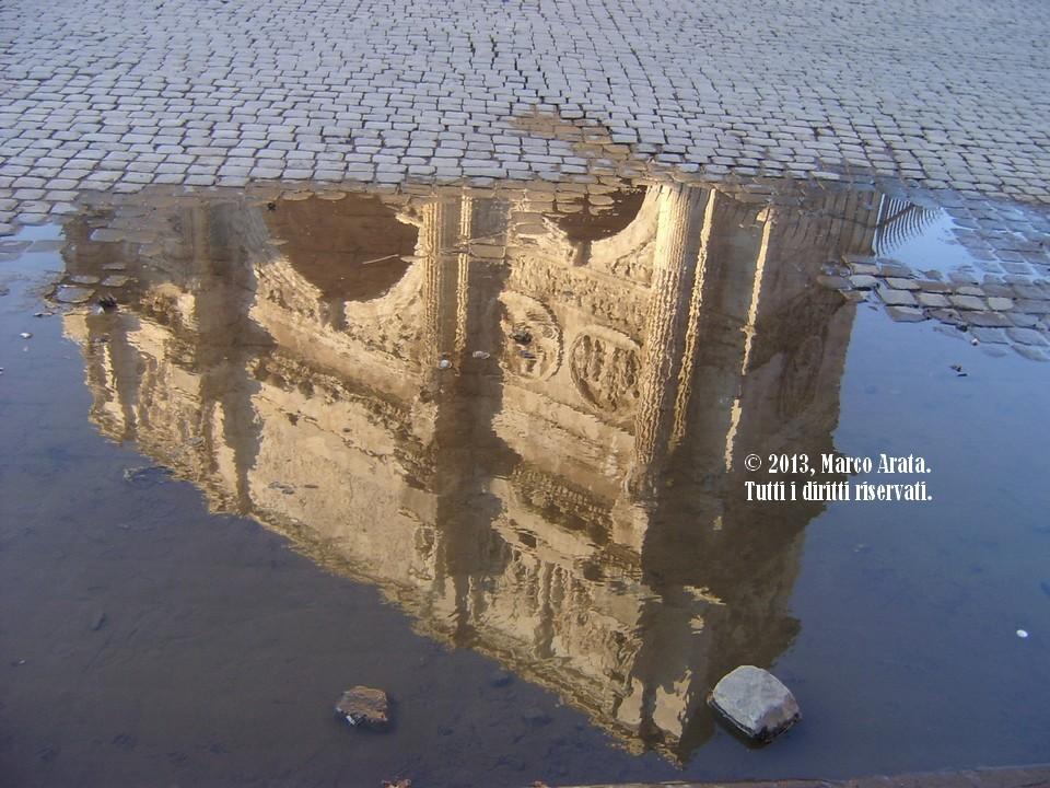 Il riflesso dell'Arco di Costantino a Roma sull'acqua circondato dal caratteristico san pietrino romano.