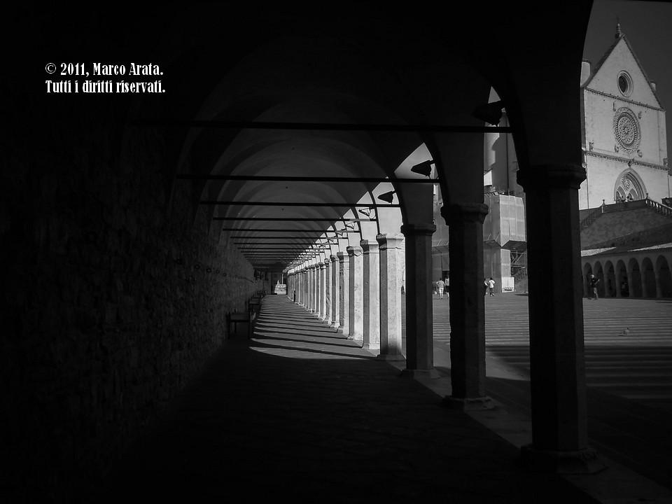 Il gioco di luci e ombre enfatizzato dal bianco e nero in questo scorcio sul portico della basilica di San Francesco d'Assisi.
