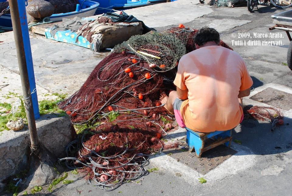Un pescatore pulisce e ripara le reti sulla banchina del molo.  Location: Favignana (TP).  Data di scatto: 25/08/2009.