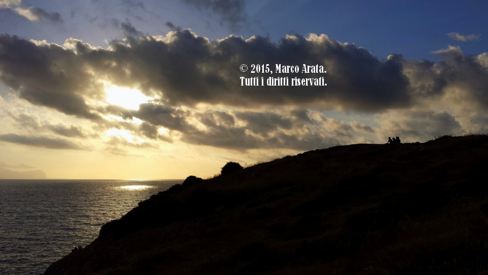 Alcuni giovani assistono allo spettacolo stupendo di un tramonto sul mare di Cala Rossa a Terrasini (Palermo). Data di scatto: 09/05/2015.