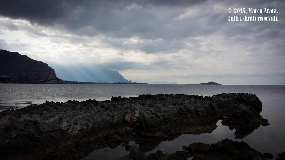 Un suggestivo paesaggio di mare. Nonostante il maltempo si avvicini, i raggi del sole riescono a filtrare la spessa coltre di nuvole nere come disegnando un arpa nel cielo. Location: Punta Barcarello (Palermo). Data di scatto: 14/11/2015.