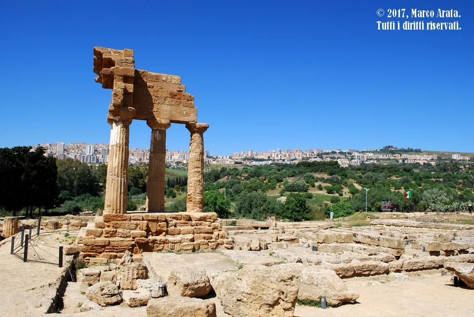 Il Tempio dei Dioscuri (o di Castore e Polluce) nella Valle dei Templi di Agrigento. Sullo sfondo una panoramica sulla città incorniciata dai colori del giardino della Kolymbethra. Data di scatto: 15/04/2017.