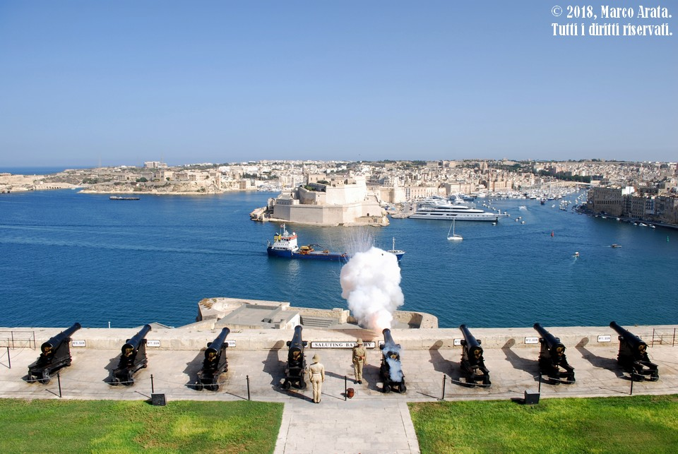 L'istante dello sparo del tramonto (16:00) da parte della Saluting Battery a Valletta, antica piattaforma cerimoniale da dove si continua a segnare il tempo due volte al giorno alle 12:00 (mezzogiorno) e alle 16:00 (tramonto) con un colpo di cannone a salve. La ripresa è stata effettuata dagli Upper Barakka Gardens, giardini pubblici panoramici che offrono una splendida vista sul Grand Harbour. Location: Upper Barakka Gardens, Valletta (Malta). Data di scatto: 06/09/2018.