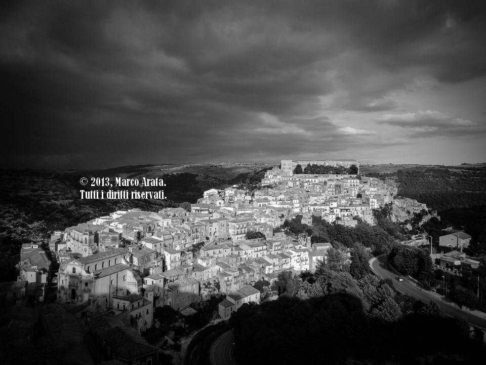 Una panoramica su Ragusa Ibla, illuminata da una lama di luce filtrante tra le nuvole di una perturbazione in arrivo. L'uso del bianco e nero esalta i contrasti tra luci e ombre. Data di scatto: 21/09/2013.